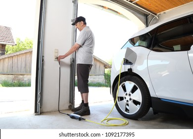 A Man Charging Electric car  at outlet at home