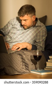 Man chatting on internet and drinking wine