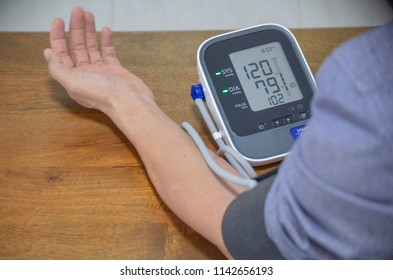 man check blood pressure monitor and heart rate with digital pressure gauge.