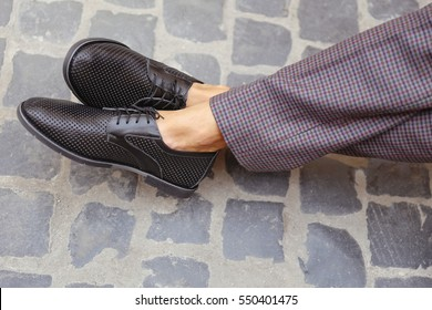 Man in checkered retro trousers in the city. Men's summer fashion, stylish men's shoes. Brown Perforated suede summer shoes with laces