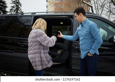 Man in checkered shirt helps woman in fur coat to get into black minivan.