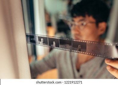 Man checking 35mm filmstrip in front of window. Photographer looking at a frames on old film. Focus on filmstrip.