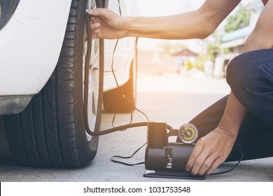 Man checking air pressure and filling air in the tires with Car eletric pump on road selective focus