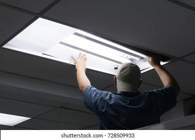 The man checking or changing Fluorescent light tube in the building.