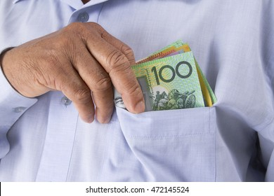 Man checking or counting Australian dollar in hand from his pocket. Notes include $100, $50, $20 and $10.