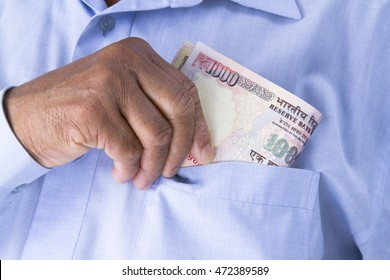 Man checking or counting Indian rupees in hand then keeping in his pocket. Notes include Rs1000, Rs100,  Rs50, Rs20 and Rs10.