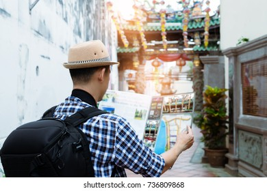 Man checking destination from a map with chinese shrine in background.Tourist and map,travel concept.
