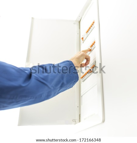 man checking the electrical fuse box at his house to see if any of the  circuit breakers have tripped - image