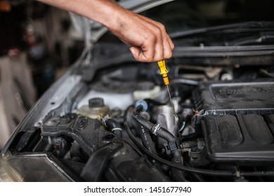 A man is checking the engine oil on a car for a replacement.