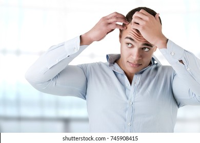 Man checking hairline, in a blue background