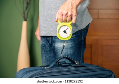 Man checking hand luggage weight using a steelyard balance by low cost airlines restrictions