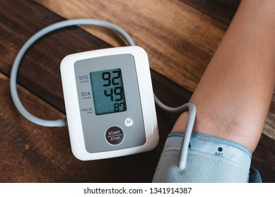 man checking his blood pressure using electronic blood pressure monitor or sphygmomanometer on a wooden table. concept of healthcare, medical instrument and stress management