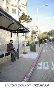 A man checking his cellphone while waiting at a bus stop