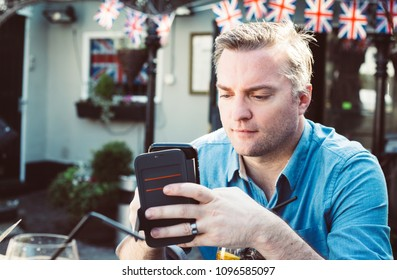 a man checking his smartphone in an English cafe