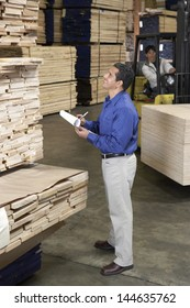 Man checking notes and laborer with forklift in the warehouse