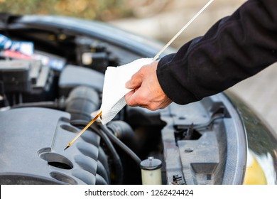 Man is checking oil level on car
