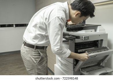 Man Checking paper jam from Photocopier with access control for scanning key card