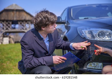 A man is checking the scratches on the front of the car. A woman is explaining something to him.
