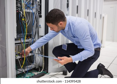 Man checking tablet pc as he is plugging cables into server in data center