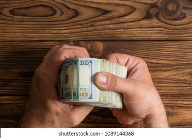 Man checking a thick stack of 100 dollar bills thumbing through them over a rustic wood table with copy space