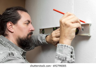 man checking wall with a level and making a tag