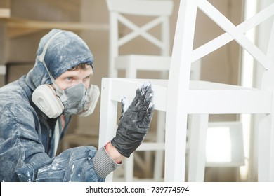 man checks the evenness of the paint application in respiratory mask. Application of flame retardant ensuring fire protection, airless spraying.