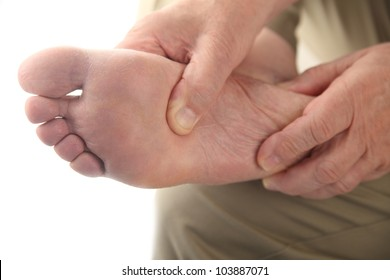 a man checks his aching foot