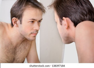 Man checks his reflection in the mirror in early morning