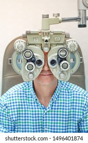 Man checks his vision on the machine checking patient vision at eye clinic or optics store. Male patient to check vision in ophthalmological clinic