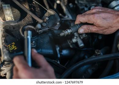 Man checks the spark plug on the old car