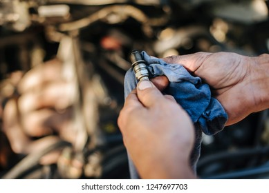 Man checks the spark plug on the old car