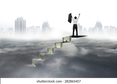 Man cheering on top of money stairs with city landscape gray cloudscape background