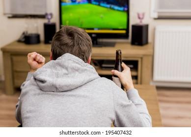 man cheering for soccer goal on tv