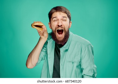 A man with a cheeseburger on a green background.