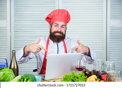Man chef searching internet recipe cooking food. Elearning concept. Chef laptop read culinary recipes. Culinary school. Hipster in hat and apron learning how to cook online. Culinary education online.