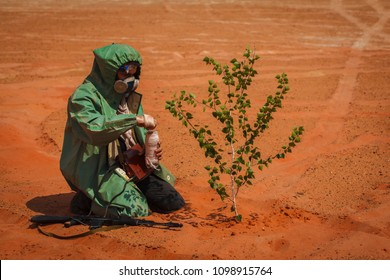 man in a chemical protection suit with arms in the desert. concept survivor after the war. cares for a tree sprout
