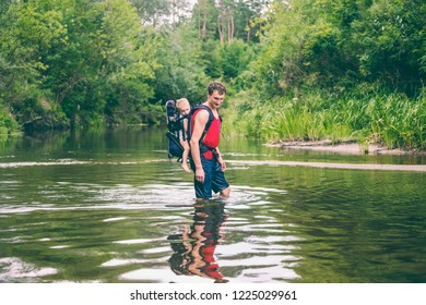 A man with a child crosses the river. The father carries the son in a backpack. Rescue from flooding. Evacuation of flood victims in Asia. Traveling with a child through the jungle. Extreme tourism.