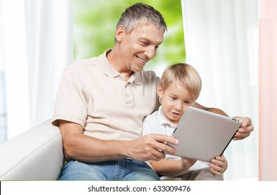 Man and child with digital tablet.