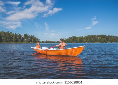 the man and the child, the girl in the boat, rowing on the lake