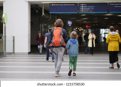 A man with a child goes to the railway station building