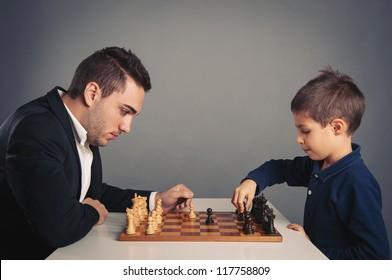 Man and child playing chess, isolated on dark background.