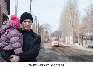 a man with a child waiting for a tram
