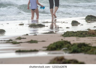 a man with a child walks along the seashore