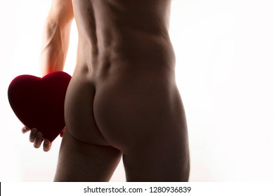 Man with chocolate gift box as romantic Valentine's Day gift, naked man holding a red velvet heart shaped box behind his back