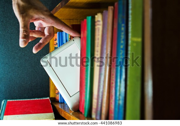 man choose ebook among paper books. new technology concept