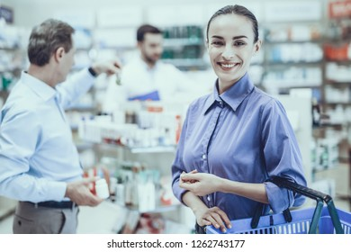 Man Choose Medicaments on Shelves. Woman is Holding Shopping Cart and Smiling. Man Holding Bottle with Pills. Pharmacist and Shelves with Medicaments on Background. People Located in Pharmacy.