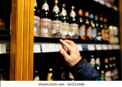 Man chooses alcoholic drinks on the counter of alcoholic department supermarket. Blurred photo.