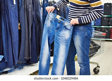 Man chooses blue jeans in shop