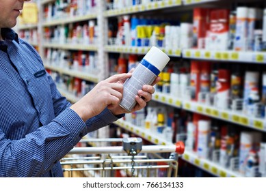 Man chooses and buys chemical products for a car in a store