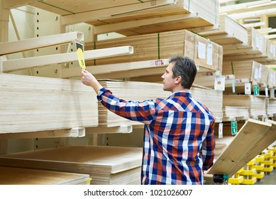 Man chooses and buys plywood in a construction supermarket